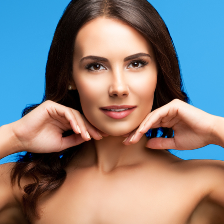 woman naked body: Portrait of beautiful young woman with naked shoulders, isolated against bright blue background. Brunette model - beauty, glamour, fashion, modeling, cosmetics, health skin and body care concept. Stock Photo