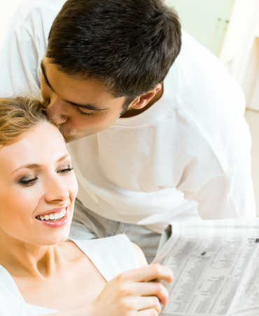 amorous: Young happy amorous couple reading newspaper at home. Love, relations, romantic concept shoot. Stock Photo
