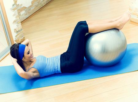 mujer sola: Mujer haciendo ejercicios de fitness feliz joven con la pelota en forma en casa