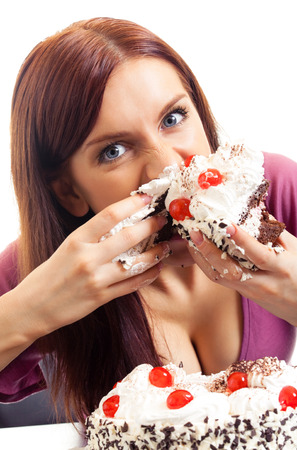 Young hungry gluttonous woman eating pie, isolated on white background. Healthy eating and dieting concept studio shot. Stock Photo