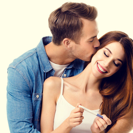 finding out: Young amorous happy couple, finding out results of a pregnancy test. Caucasian models - in love, relationship, dating, happy lovers, family concept. Stock Photo
