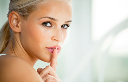 Portrait of young woman with finger on lips, at home. Secret hand sign gesture. Stock Photo