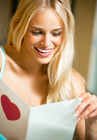 only 1 woman: Young happy smiling woman, reading valentine card at home. Love, romantic, relations theme concept. Stock Photo