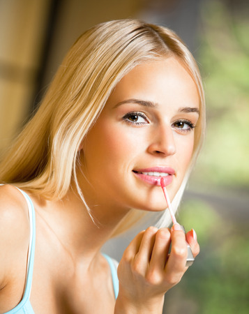 wellfare: Portrait of young happy smiling woman applying lipstick at home. Beauty and fashion theme concept.