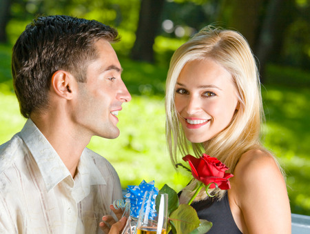flirtation: Young happy couple with champagne, gift and rose, outdoors. Love, flirt, romantic, relations, celebration theme concept. Stock Photo