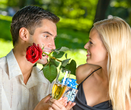 flirt: Funny young happy couple with gift and rosa, outdoors. Love, flirt, romantic, relations, celebration theme concept.