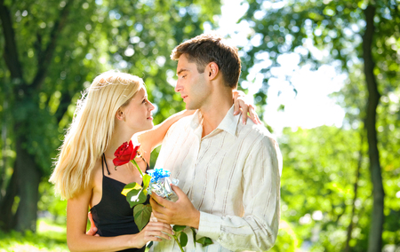 flirtation: Young happy couple with gift and rose, outdoors. Love, flirt, romantic, relations, celebration theme concept.