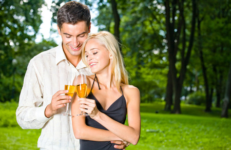 flirtation: Young happy couple celebrating with champagne, outdoors. Love, flirt, romantic, relations, celebration theme concept.
