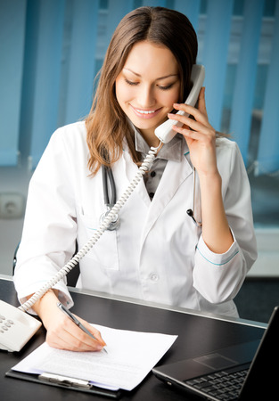 Portrait of happy smiling cheerful young female doctor on phone at office
