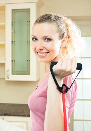 Portrait of young woman in sportswear, doing fitness exercise with expander, indoors. Individual sport, weight lossing and healthy lifestyle concept.
