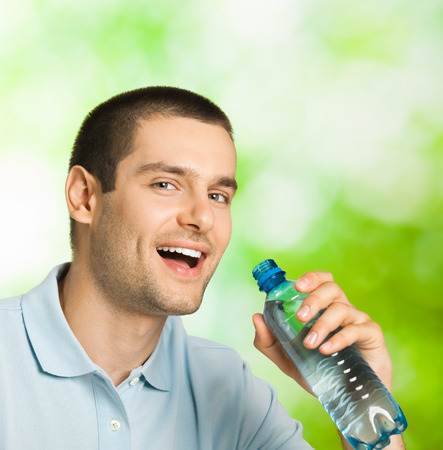 man drinking water: Young happy smiling man drinking water, outdoors
