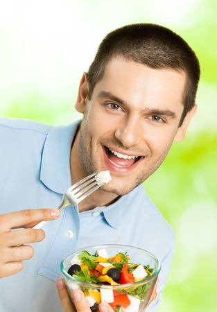 eating salad: Portrait of young happy man eating salad, outdoors. Healthy eating and diet theme concept.