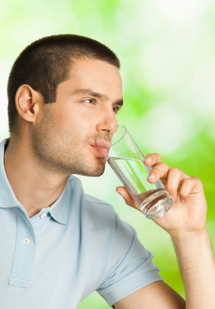man drinking water: Young man drinking water, outdoors Stock Photo