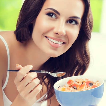 Cheerful beautiful woman eating muslin, indoors. Healthy eating, beauty and dieting concept.