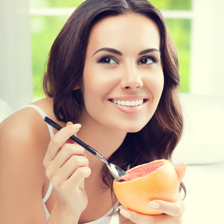 Cheerful smiling woman eating grapefruit at home. Healthy eating, beauty and dieting concept.