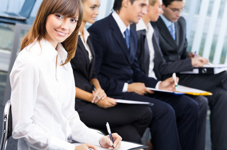 Portrait of happy smiling businesswoman and colleagues on background, at conference, meeting or presentation. Success in business, partnership and teamwork theme concept. Stock Photo