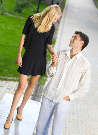 flirtation: Young happy amorous couple together, outdoors. Love, flirt, romantic, relations theme concept.