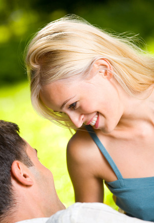 flirtation: Young happy smiling couple outdoors together. Love, flirt, romantic, relations theme concept.