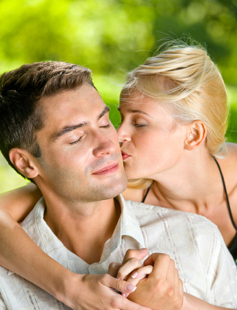 flirtation: Young happy amorous embracing couple, outdoors. Love, flirt, romantic, relations theme concept.