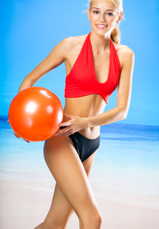 body shape: Young beautiful happy smiling blond woman in sportswear playing with red gym ball on sea beach