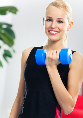 fitball: Portrait of young woman in sportswear, doing fitness exercise with dumbbell on fit ball, indoors. Healthy lifestyle, weight lossing and sporting theme concept shot. Stock Photo