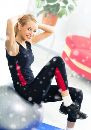 fit ball: Portrait of young happy smiling woman in sportswear, doing fitness exercise with fit ball, indoors. Healthy lifestyle, weight lossing and sporting theme concept shot. Over snow. Stock Photo