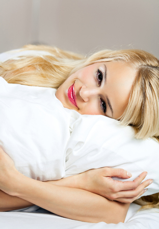 lazyness: Portrait of young happy smiling woman waking up at bedroom. Healthy lifestyle concept.