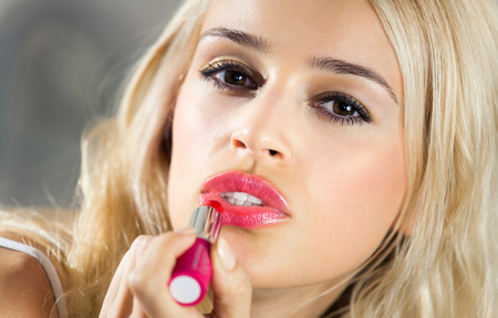 wellfare: Portrait of young woman applying lipstick at home. Beauty and make up concept.
