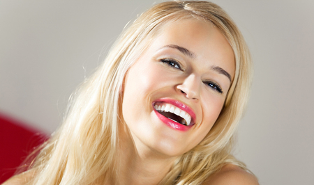 young woman smiling: Portrait of young happy smiling attractive woman, indoors. Cheerful emotions concept.