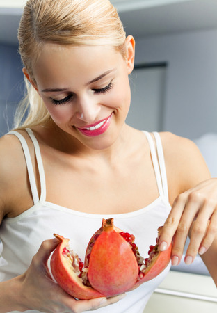 only: Young happy smiling woman with pomegranate indoors. Healthy eating and diet theme concept. Stock Photo