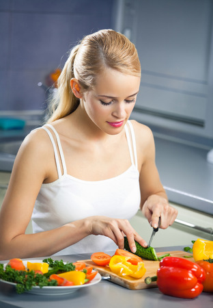 woman diet: Young happy woman making salad at domestic kitchen. Healthy eating and diet theme concept.