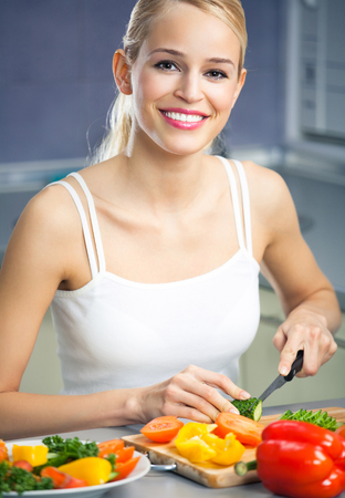 Young happy woman making salad at domestic kitchen. Healthy eating and diet theme concept.