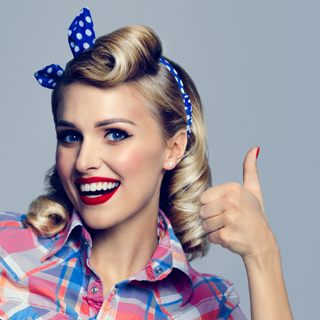 Portrait of beautiful young happy smiling woman, showing thumb up gesture, dressed in pin-up style. Caucasian blond model posing in retro fashion and vintage concept studio shoot. Square composition. Stock Photo