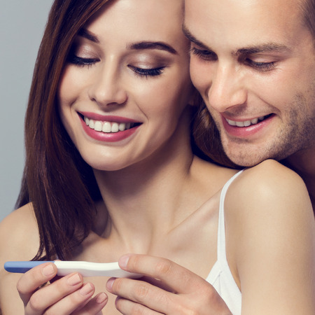 finding love: Beautiful young amorous couple, finding out results of a pregnancy test. Caucasian white models in love, relationship, dating, happy lovers, concept shot, against grey background. Square composition. Stock Photo