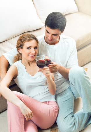 Young happy amorous couple celebrating with redwine at home