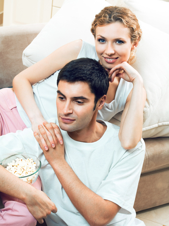 pareja viendo tv: Young couple watching TV together at home