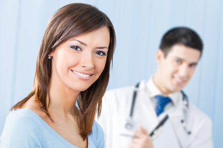 Happy female patient and doctor at office. Focus on woman. Heathcare, medicine, diagnosis and treatment concept.