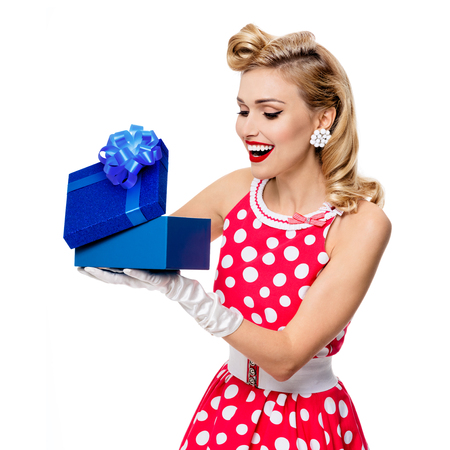 upsweep: Portrait of beautiful young happy woman dressed in pin-up style red dress in polka dot and gloves, isolated over white background. Caucasian blond model posing in retro fashion shoot. Square composition.
