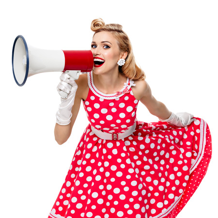 Portrait of woman holding megaphone, dressed in pin-up style red dress in polka dot and gloves, isolated on white background. Caucasian blond model posing in retro fashion vintage shoot. Square composition.