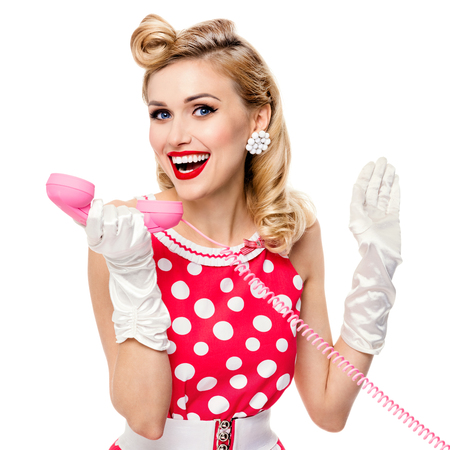 Portrait of beautiful happy woman with phone, dressed in pin-up style red dress in polka dot and white gloves, isolated over white background. Caucasian blond model posing in retro shoot. Square composition. Stock Photo