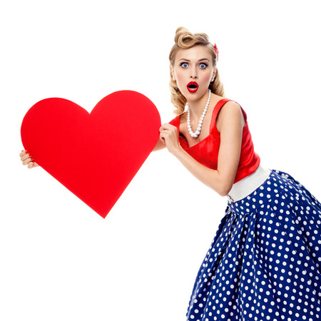 clothes pins: Woman holding heart symbol, dressed in pin-up style dress with polka dot, isolated over white background. Caucasian blond model posing in retro fashion and vintage concept shoot. Square composition.