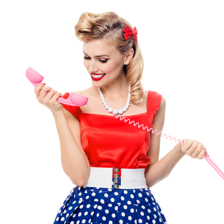 Beautiful woman with phone dressed in pin-up style dress in polka dot, isolated over white background. Caucasian blond model posing in retro fashion and vintage concept. Square composition. Stock Photo