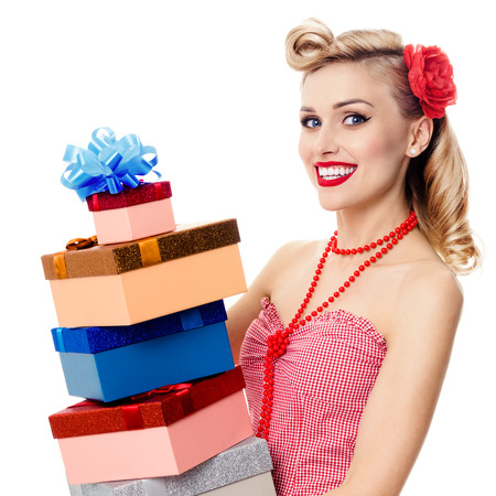 Beautiful young happy smiling woman in pin-up style clothing, holding gift boxes, isolated over white background. Caucasian blond model posing in retro fashion and vintage concept shoot. Square composition. Stock Photo
