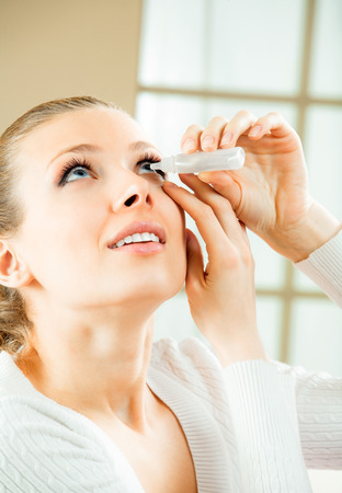 Photo of young woman dripping eye with eyes drops at home Stock Photo
