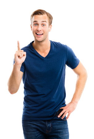 idea: I have idea! Smiling young man in blue casual smart clothing, showing up on something or copyspace for text or slogan, or making idea hand sign gesture, isolated against white background. Emotions and success concept.