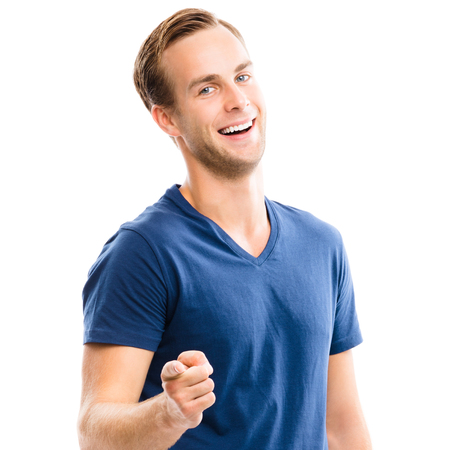 What about You? Cheerful young man showing to you with index finger, isolated over white background. Pointing at something over finger. Emotions and success concept.