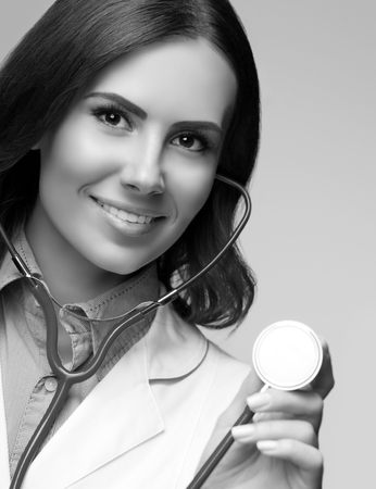 doctor female: Portrait of happy smiling female doctor with stethoscope in hand. Healthcare and medical concept. Black and white.