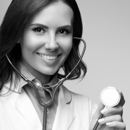 healthcare portrait: Portrait of happy smiling female doctor with stethoscope in hand. Healthcare and medical concept. Black and white.