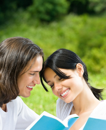 Young happy smiling couple reading a book together, outdoors. Love, flirt, romantic, relations, education concept.