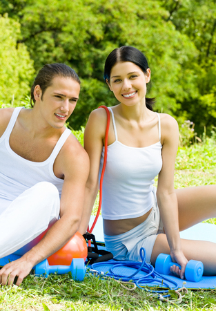 pareja saludable: Young happy smiling couple in sport wear on workout, outdoors. Healthy lifestyle, weight lossing and fitness concept.